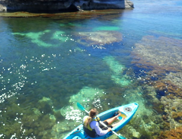 Girl kayaking in bay in Rottnest